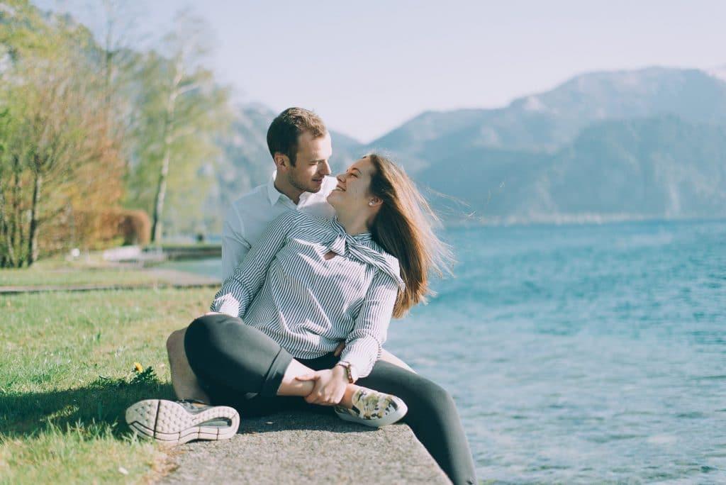 Verliebte am See auf Ufermauer beim Fotoshooting