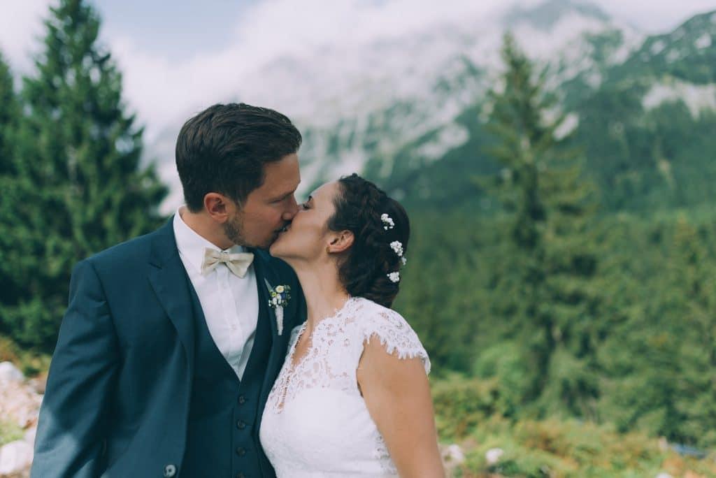 Brautpaar küsst sich in den Bergen