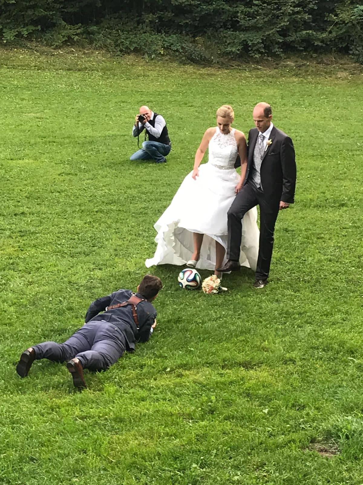 Hochzeitsfotografin Barbara Weber liegt vor einem Brautpaar in der Wiese